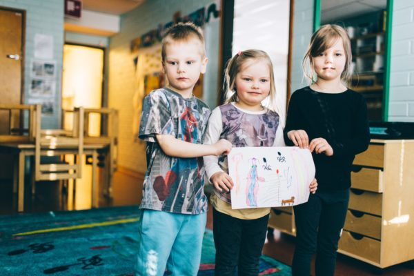 In the picture are children from the Linnainmaa daycare centre, Mio Saarinen, Ellen Äppelqvist and Olivia Hyle, standing on a mat they helped design. The colourful mat is based on a drawing made by the children, who really let their imagination fly!